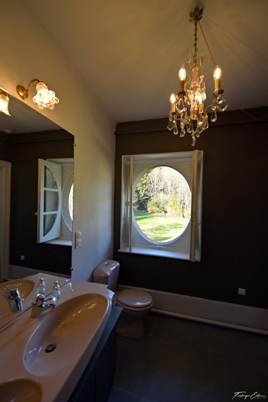 lavabo et fenetre vue sur le terrain extérieur